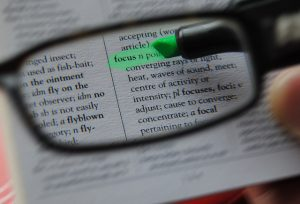 "Pair of glasses focussing on the word ""focus"" in dictionary."